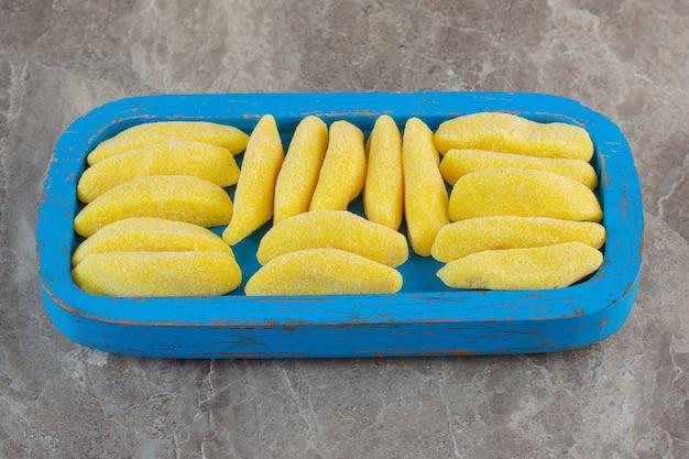 青い木の板に黄色いフルーツの歯ごたえのあるキャンディーの山。