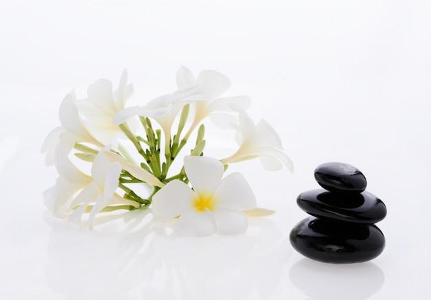 Куча камней дзен и цветок франжипани, изолированные на белом