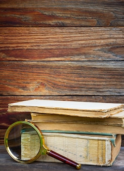 A pile of old books and magnifier