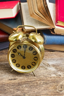 Pile of old books with golden antique alarm clock