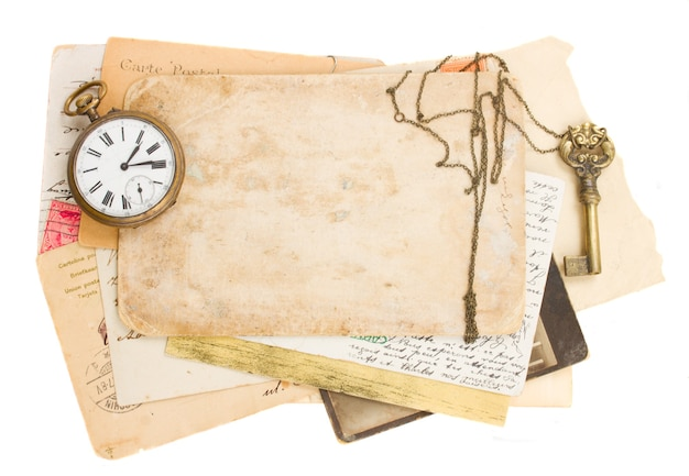 Pile of old papers with antique clock and key isolated on white background