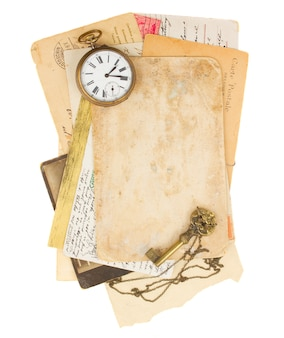 Pile of old photos and papers with antique clock and key isolated on white background