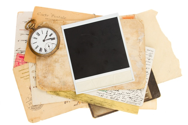 Pile of old photos with antique clock isolated on white background