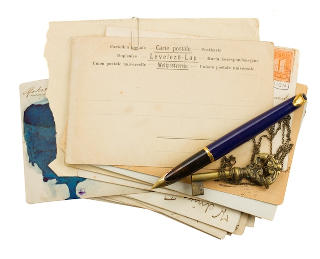Pile of old postcards with quill pen isolated on white background