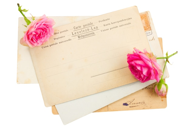 Pile of old postcards with rose buds isolated on white background
