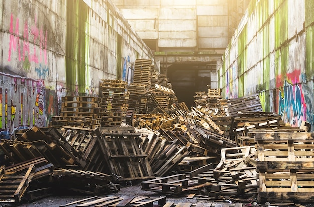 A pile of old wooden pallets on an abandoned warehouse.