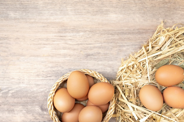 Pile of organic fresh and raw hen chicken eggs for sale on the wooden table.