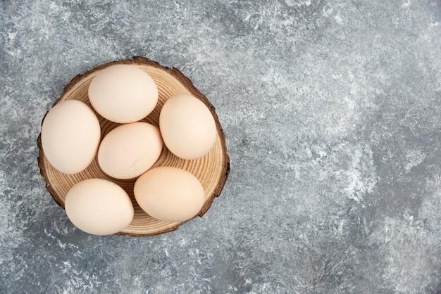 Pila di uova crude fresche organiche poste sul pezzo di legno.
