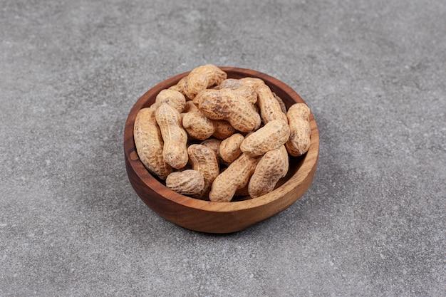 Pila di arachidi organiche nella ciotola di legno