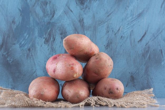 Pile of organic red potatoes on sack .
