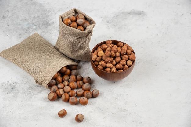 Pila di organico sgusciate e noccioli di nocciole in tela e in una ciotola.