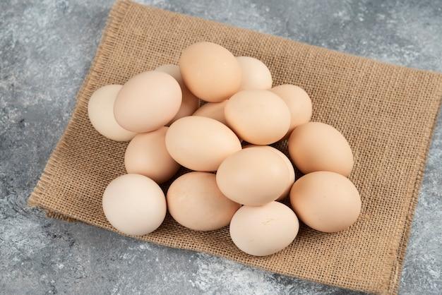 Pila di uova crude organiche con tovaglia sulla superficie in marmo.