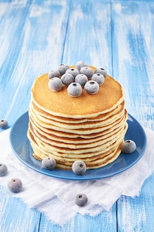 A pile of pancakes stuffed with frozen blueberry on a blue plate on a blue background sprinkled with powdered sugar