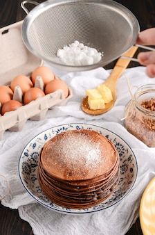 A pile of pancakes with a wooden spoon of butter, eggs, on a rustic wooden table.