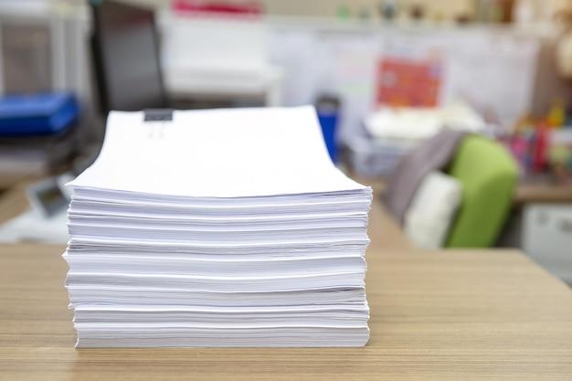 Pile of paper on office desk.