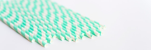 Pile of paper striped white and green drinking straws for party on white background. space for text