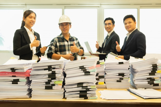 Pile of paperwork on table with group of happy business people standing.