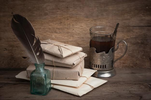 Свая пакет, обернутый коричневой крафт-бумагой и пером в чернильнице