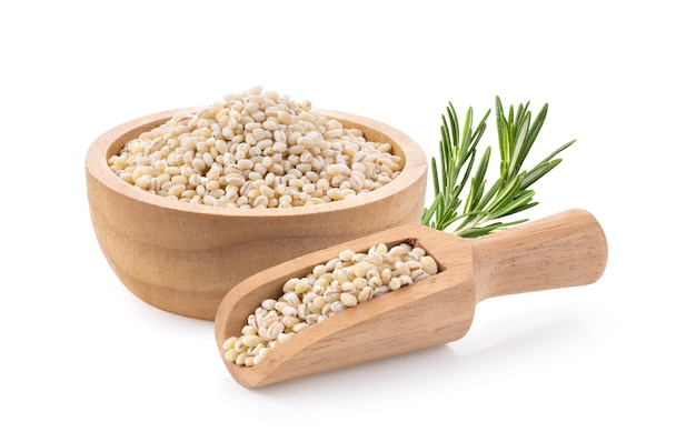 Pile of pearl barley in wood bowl scoop isolated on white surface