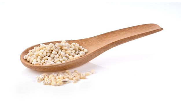 Pile of pearl barley in wood scoop isolated on white