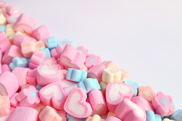 Pile of pink heart shaped and pastel color flower shaped marshmallow candies with free space for design