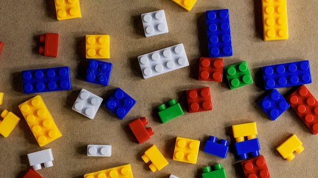 Pile of plastic building blocks on brown paper background