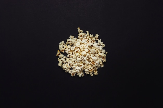 A pile of popcorn on a black background. flat lay, top view.