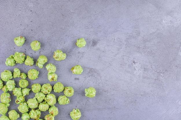 Un mucchio di caramelle popcorn si è rovesciato su uno sfondo di marmo. foto di alta qualità