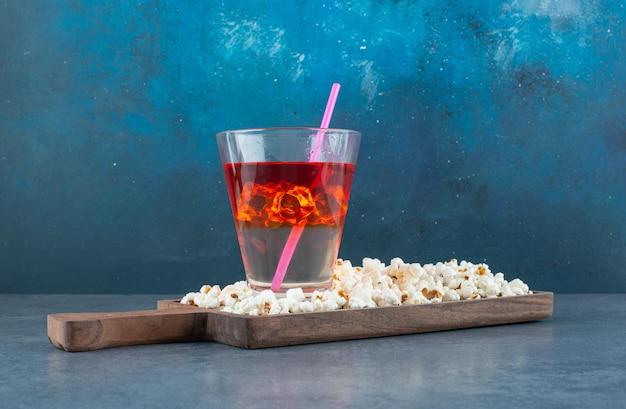 Pila di popcorn e un bicchiere di bevanda ghiacciata su una tavola di legno sul blu