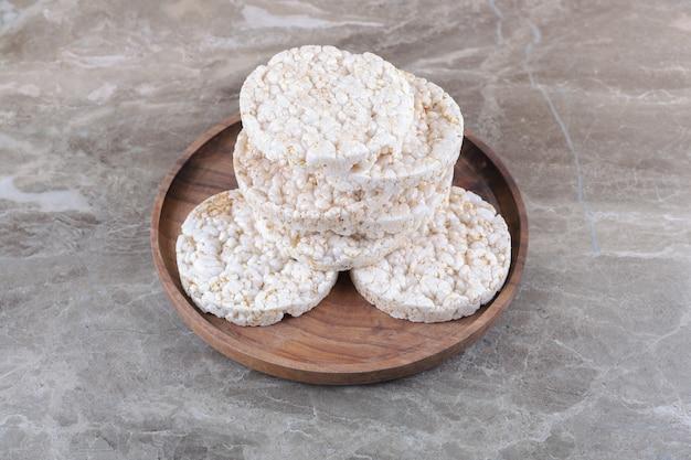 Un mucchio di torte di riso soffiato sul vassoio di legno, sullo sfondo di marmo.
