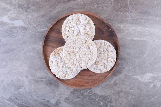 Un mucchio di gallette di riso soffiato sul vassoio di legno, sulla superficie di marmo