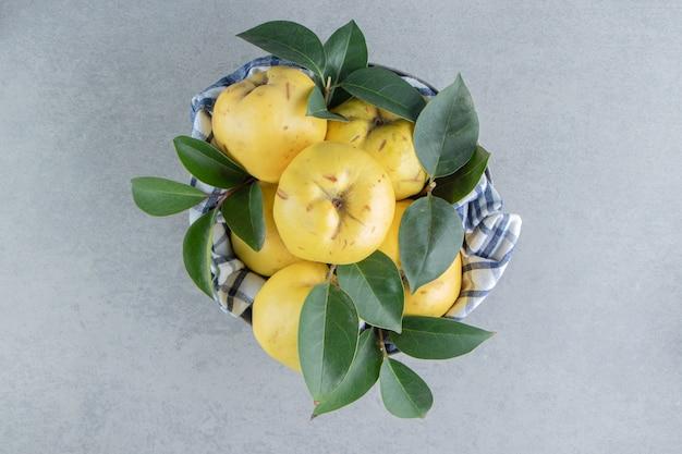 Un mucchio di mele cotogne e foglie su marmo