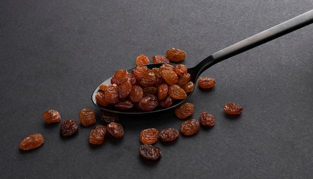 Pile of raisins in spoon on black