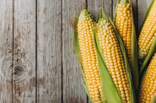 Pile of raw corns on grey wooden background