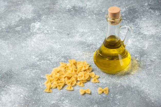 Pila di materie farfalle di pasta con una bottiglia di olio d'oliva su sfondo marmo.