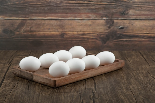 Pile of raw fresh white eggs on wooden plate.
