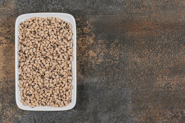 Mucchio di fagioli bianchi crudi sul piatto bianco.