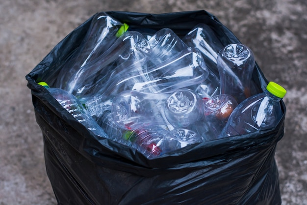 Pile recyclable plastic bottles in trash bag