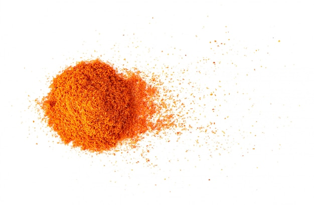 Pile of red paprika powder on white wall.