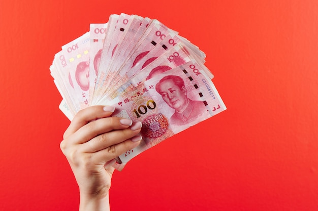 A pile of rmb banknotes of chinese yuan money in a female hand on a red
