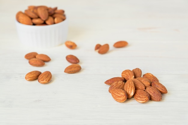 Pile of roasted almonds on white wooden table, close up, copy space