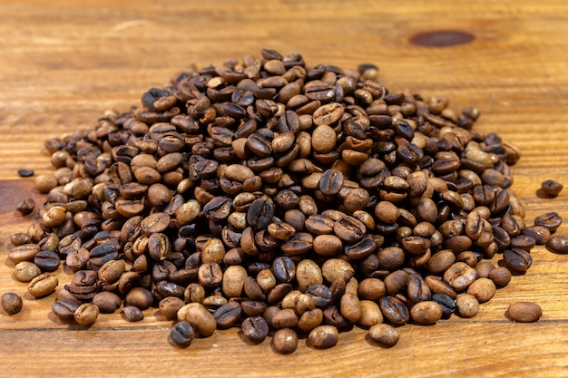 Pile of roasted artesanal gourmet coffee beans pattern on a wood table