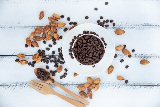 Pile of roasted coffee beans in white cup of coffee  on white wood
