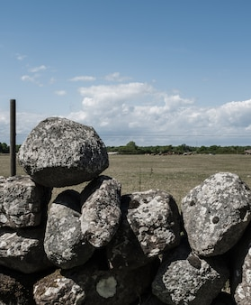 Pile of rocks stacked on top of each other as a fence in a field