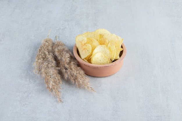 Pile of salted crispy chips placed in bowl on stone.