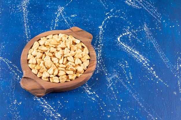Pila di cracker salati a forma di cuore posti su una tavola di legno