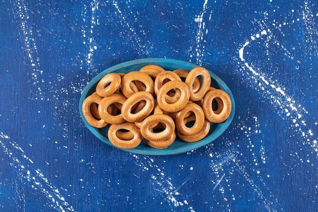 Pile of salted round pretzels placed on blue plate.