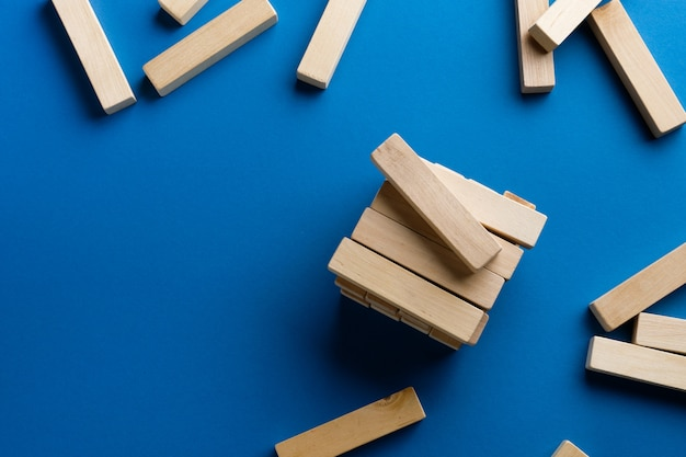 A pile of scattered wooden blocks on a blue surface. construction game. the broken tower.
