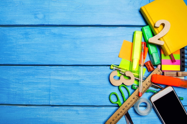A pile of school supplies on a blue wooden table background.