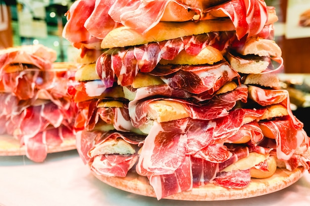 Pile of serrano ham sandwiches, typical spanish sandwich, for tourists.
